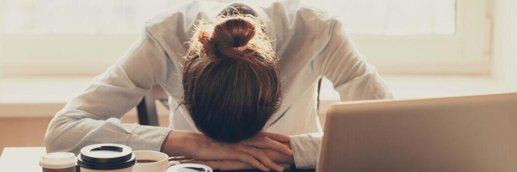 Stressad person lutar huvudet mot bordet