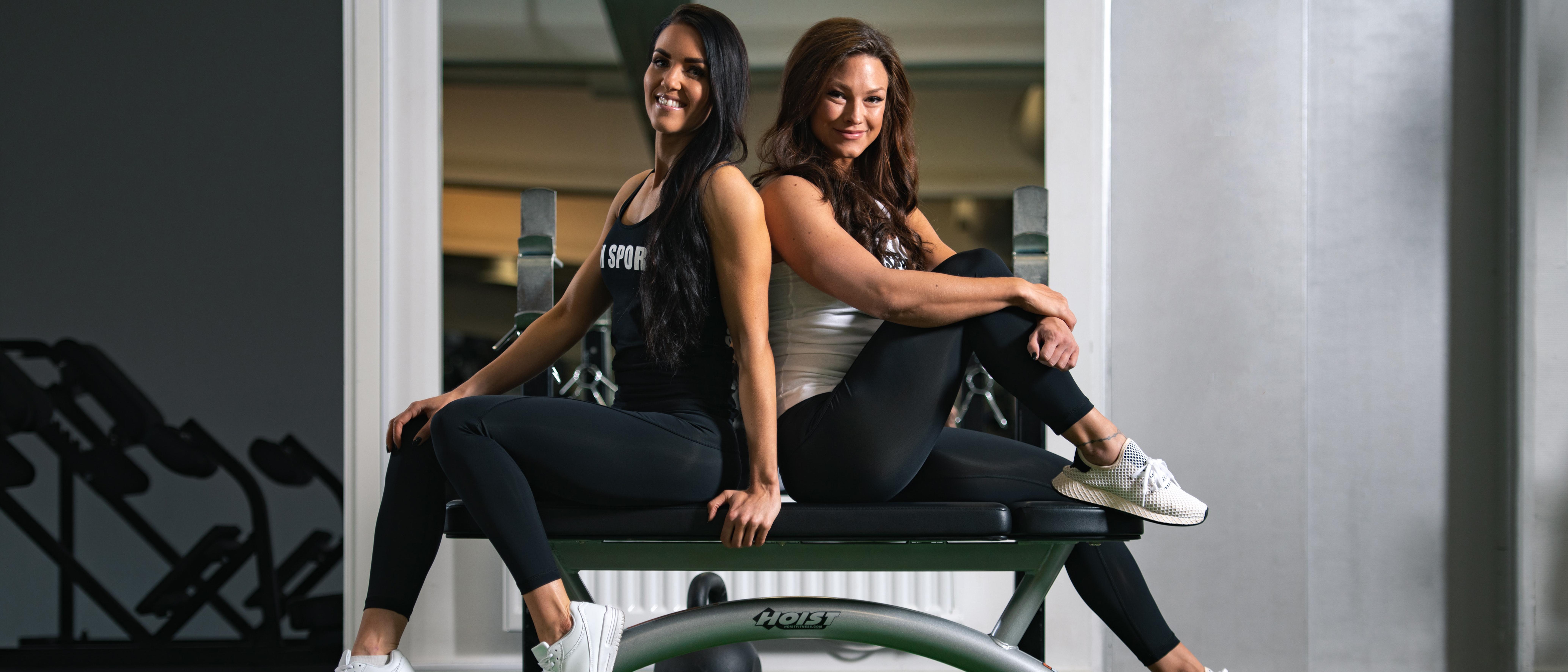 Två kvinnor sitter rygg i rygg på en bänk på gymmet