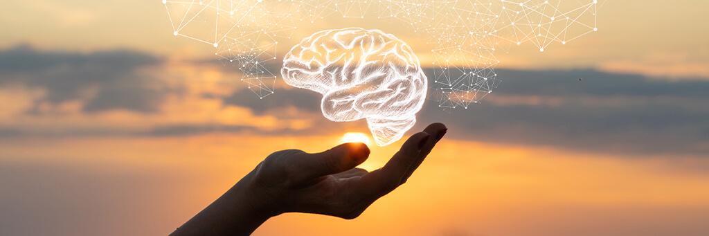 Hand som håller en hjärna i hologram i solnedgången