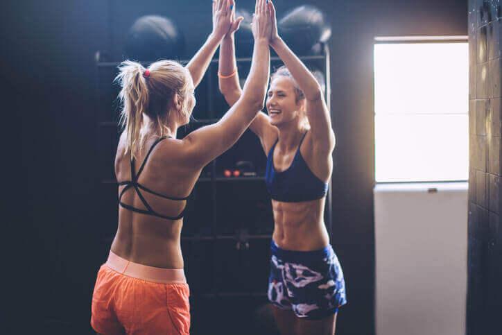 To personer giver hinanden en high five på fitnesscentret