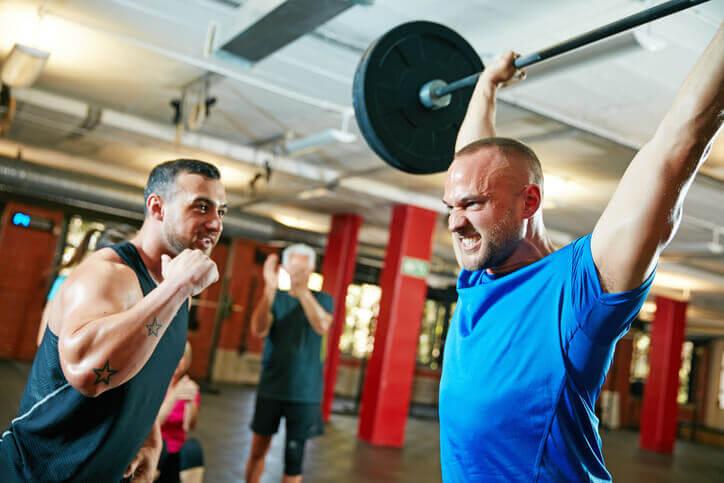 To personer trener styrke på treningssenteret