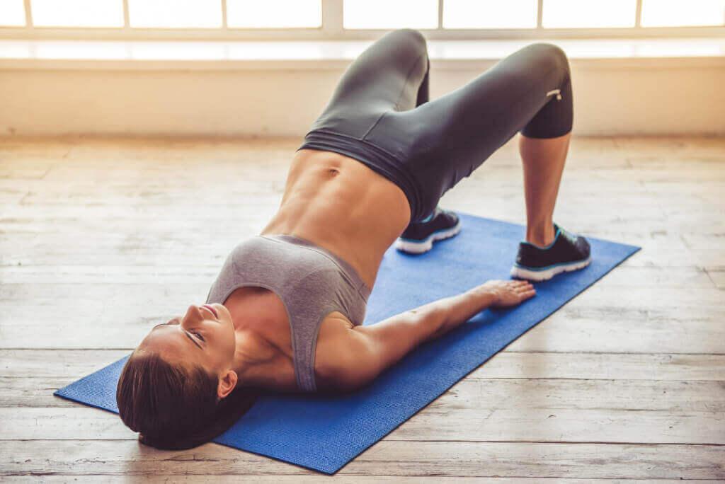 En kvinde, der træner på en yogamåtte
