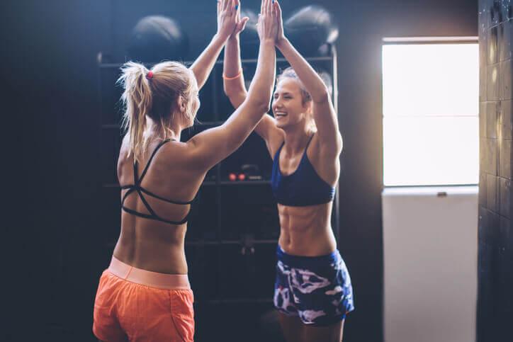 To jenter feirer suksess på treningssenteret