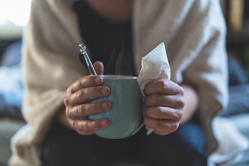 En förkyld person som håller en varm kopp te och papper