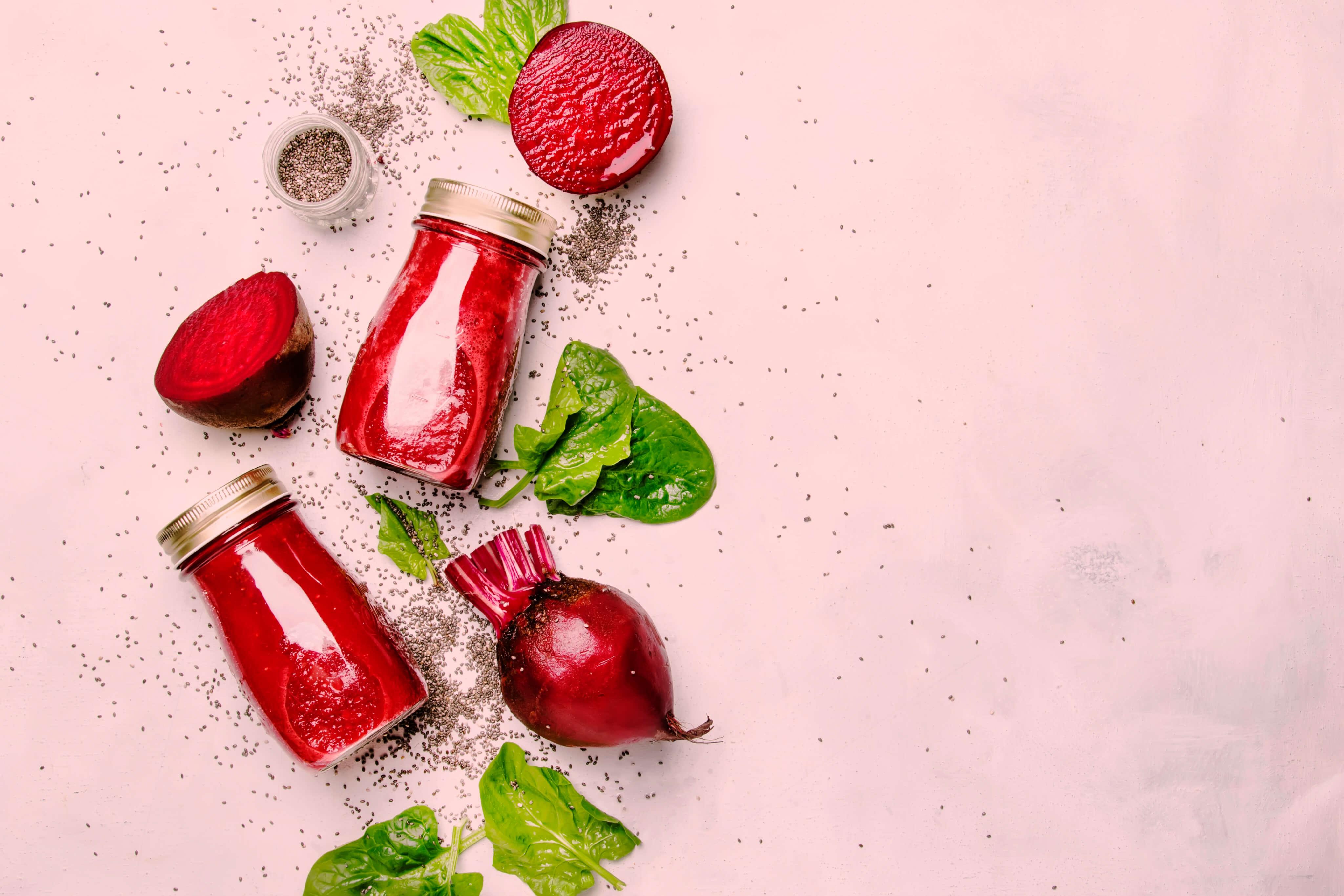 Rödbetor, rödbetsjuice, frön och salladsblad mot ljusrosa bakgrund