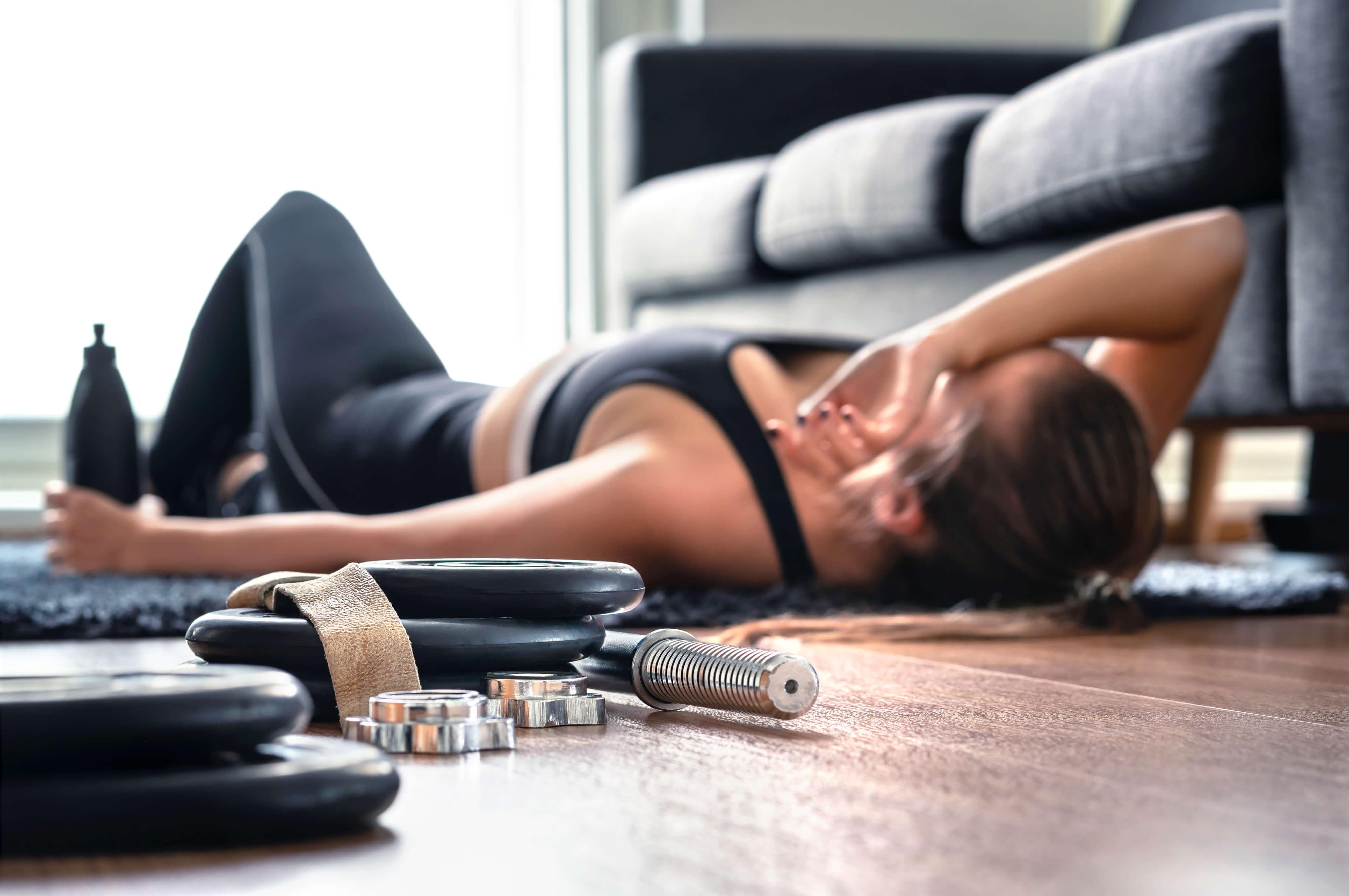 Kvinna som är trött efter träning ligger på golvet