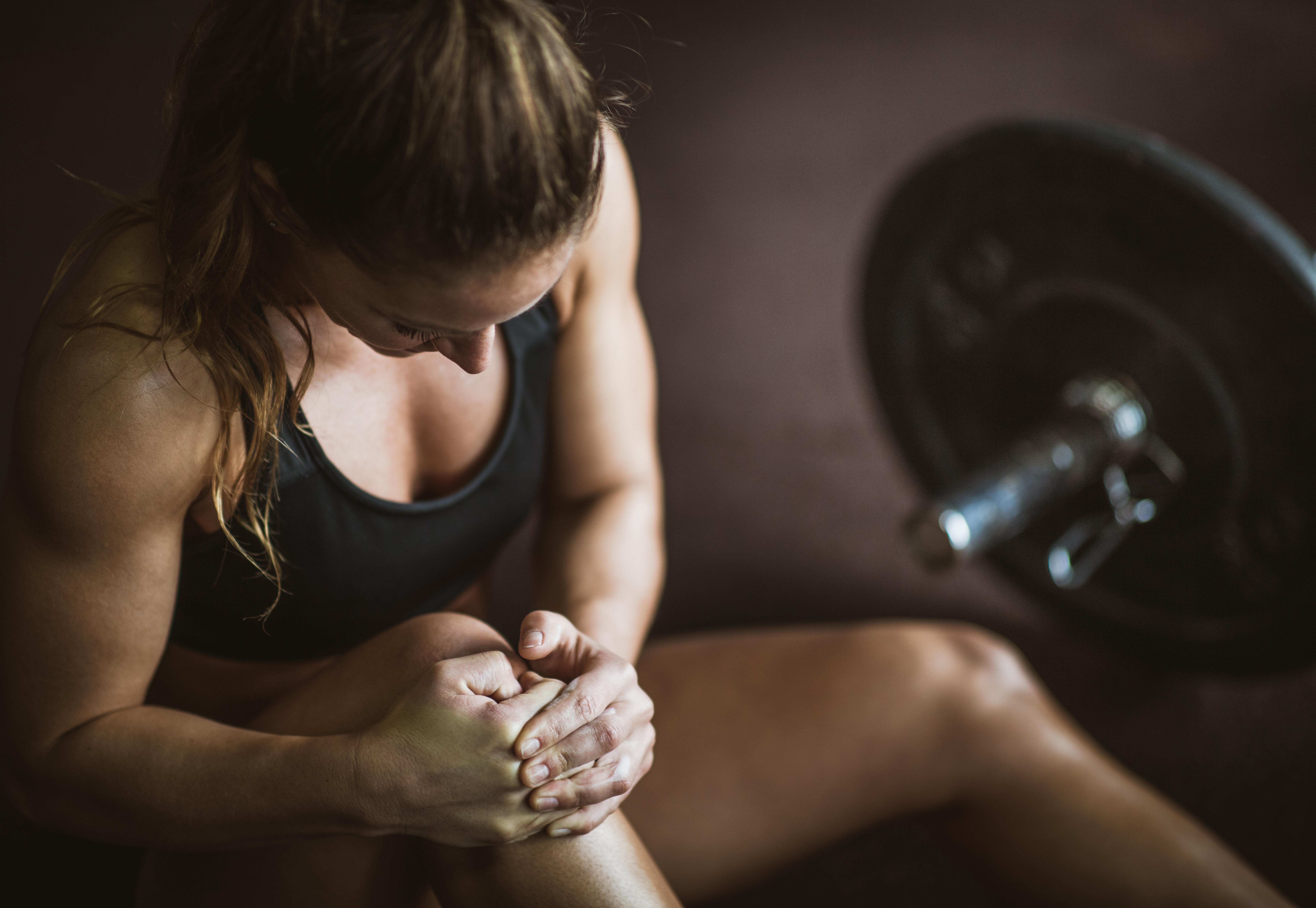 Atletisk kvinna håller om sitt knä i smärta