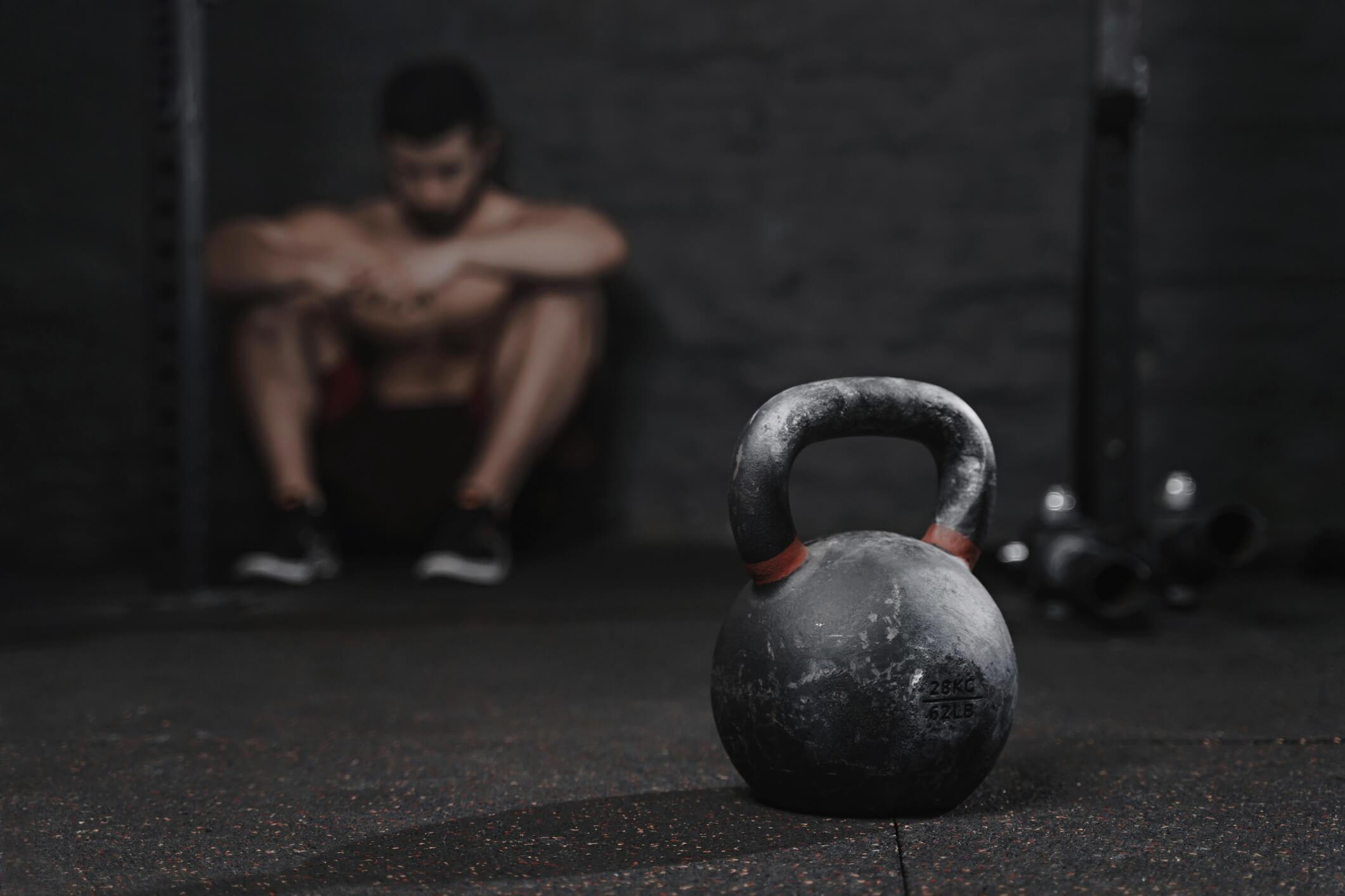 Man sitter i gym utmattad